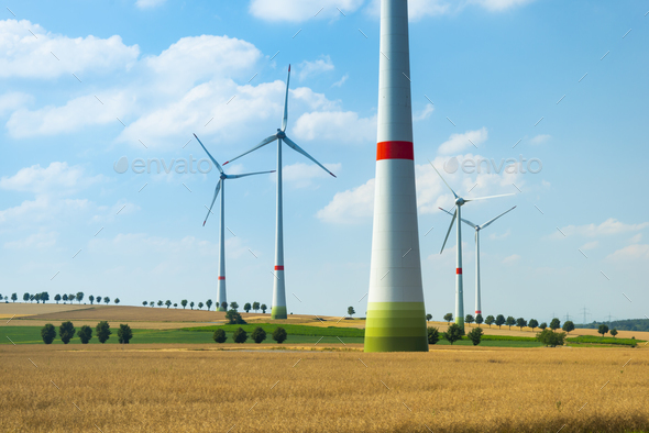 Wind turbines and agricultural fields on a summer day - Stock Photo - Images