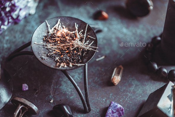 Burning herbs on a witch's altar for a magical ritual among crystals and black candles. - Stock Photo - Images