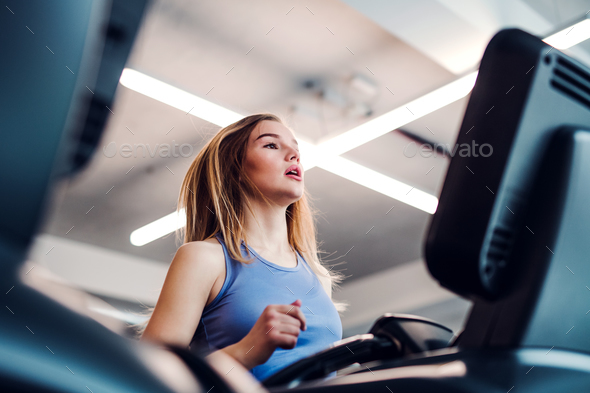 A portrait of young girl or woman doing cardio workout in a gym. - Stock Photo - Images