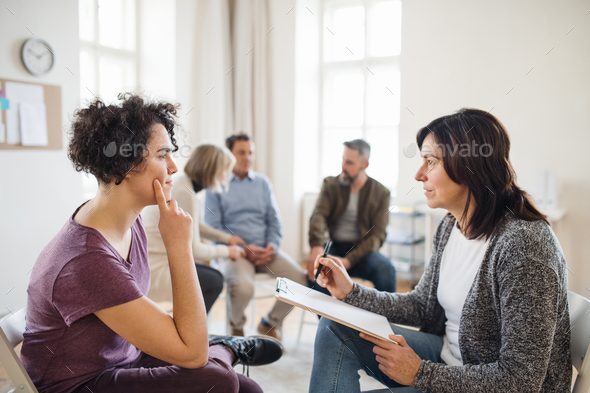 Senior counselor with clipboard talking to a woman during group therapy. - Stock Photo - Images
