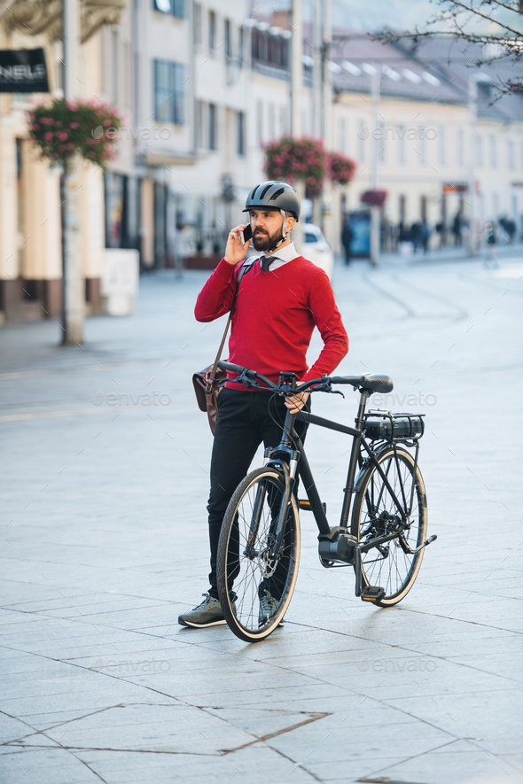 Hipster businessman commuter with bicycle and smartphone on the way to work in city. - Stock Photo - Images