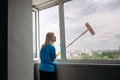 View of young blonde girl cleaning large open window - PhotoDune Item for Sale