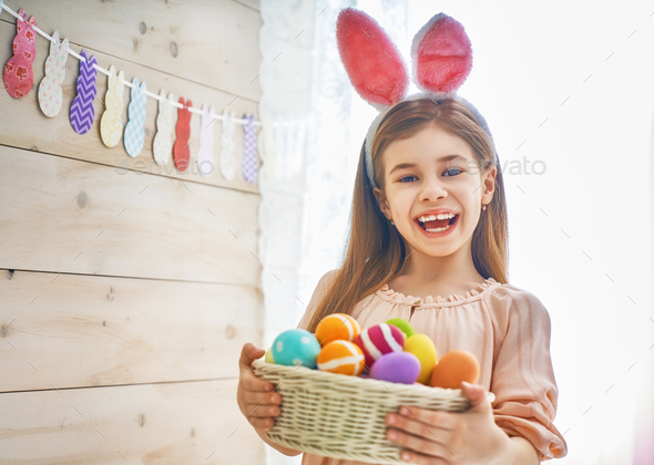 Girl holding basket with painted eggs - Stock Photo - Images