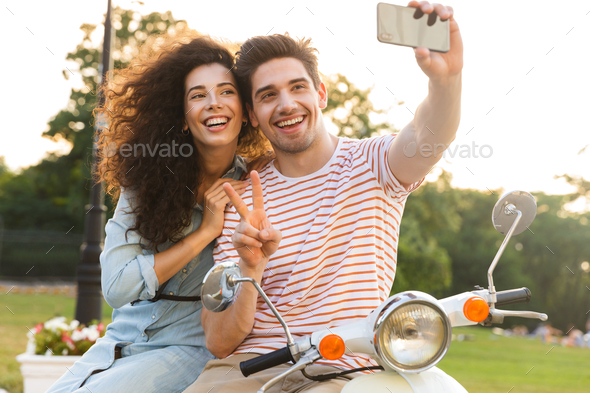 Photo of cute couple man and woman taking selfie on mobile phone - Stock Photo - Images
