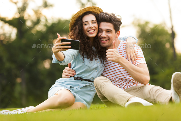 Image of joyous couple man and woman 20s sitting on green grass - Stock Photo - Images