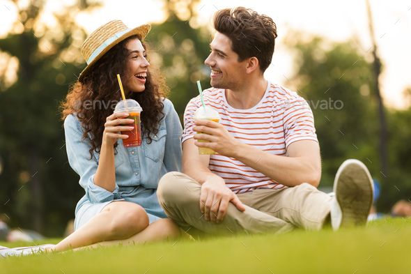Image of young couple man and woman 20s sitting on green grass i - Stock Photo - Images