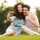 Image of joyous couple man and woman 20s sitting on green grass - PhotoDune Item for Sale
