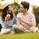 Image of young couple man and woman 20s sitting on green grass i - PhotoDune Item for Sale
