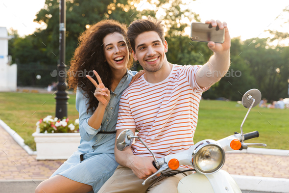 Photo of pretty couple man and woman taking selfie on mobile pho - Stock Photo - Images