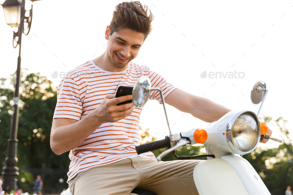 Portrait of beautiful man 20s sitting on motorbike in city stree - Stock Photo - Images