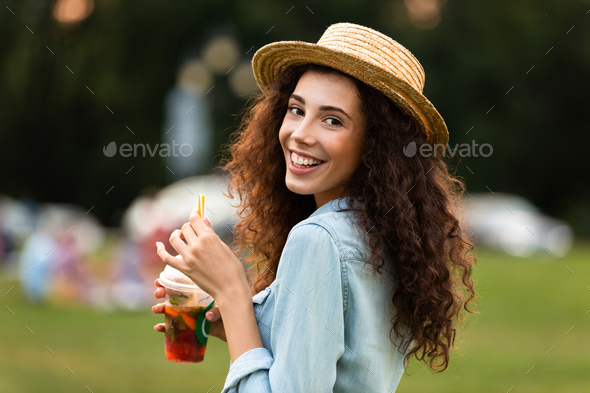 Image of brunette woman 20s wearing straw hat, smiling and drink - Stock Photo - Images