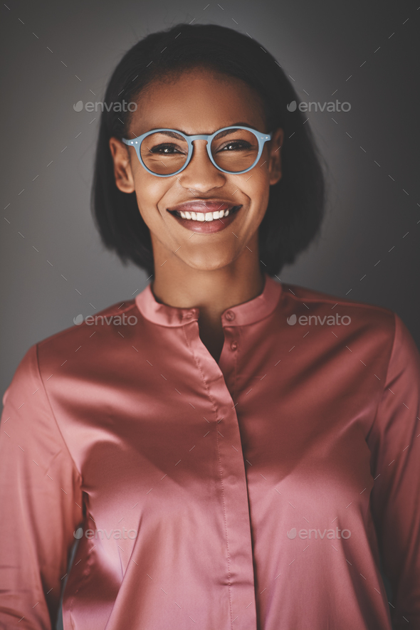 Young African businesswoman smiling confidently against a gray background - Stock Photo - Images