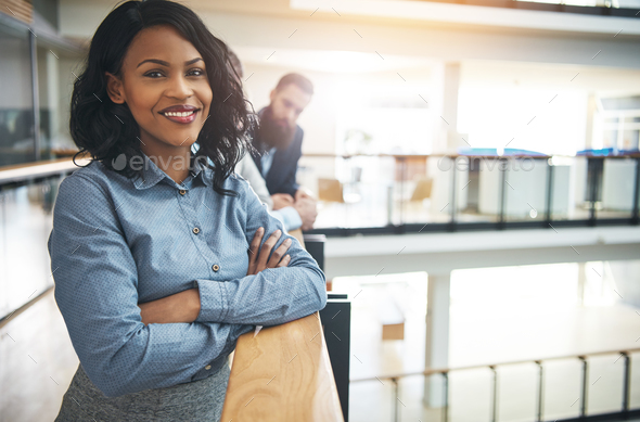 Smiling young businesswoman standing in the hallway of an office - Stock Photo - Images