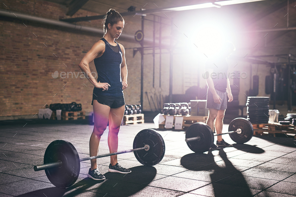 Two sportsmen standing near barbells in gym - Stock Photo - Images