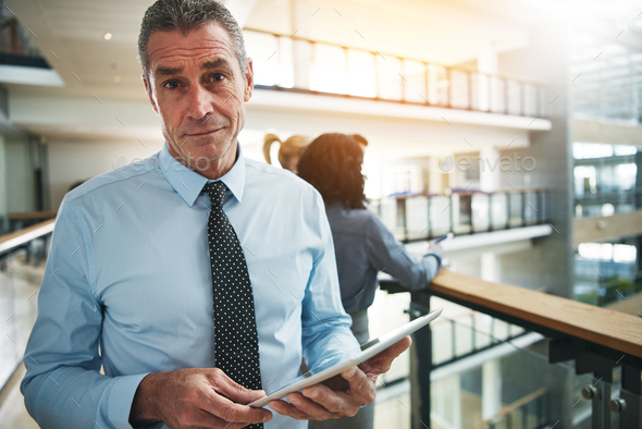 Focused businessman standing with a tablet in an office corridor - Stock Photo - Images