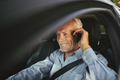 Smiling senior man driving his car talking on a cellphone - PhotoDune Item for Sale