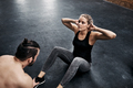 Fit young woman doing crunches with a gym partner - PhotoDune Item for Sale