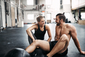 Two people sitting on a gym floor after working out - PhotoDune Item for Sale