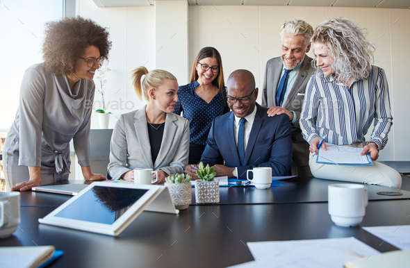 Smiling colleagues working together at a table in an office - Stock Photo - Images