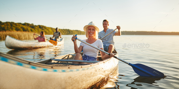 Smiling woman canoeing with friends on a lake in summer - Stock Photo - Images