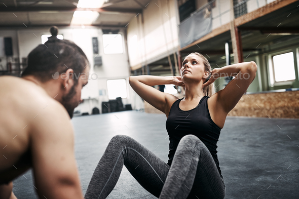 Young woman doing sit ups with a gym partner - Stock Photo - Images