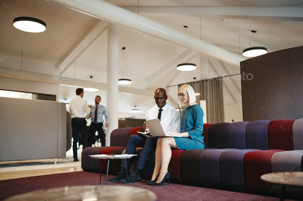 Two diverse office colleagues working online together on a sofa - Stock Photo - Images