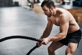Fit young man swinging ropes during a gym workout - PhotoDune Item for Sale