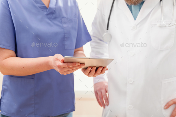 Doctors discussing report about a patient at tablet computer in hospital - Stock Photo - Images