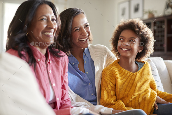 Three generation family female family group sitting on a sofa in the living room watching TV - Stock Photo - Images