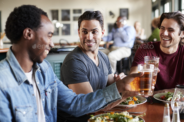 Group Of Male Friends Making A Toast At Meal In Restaurant - Stock Photo - Images