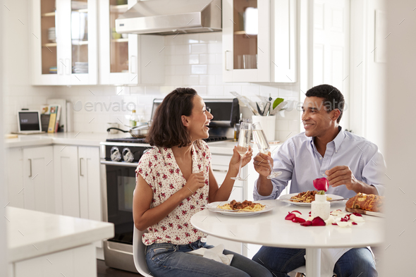 Young couple sitting at the table in their kitchen making a toast whilst eating a meal - Stock Photo - Images