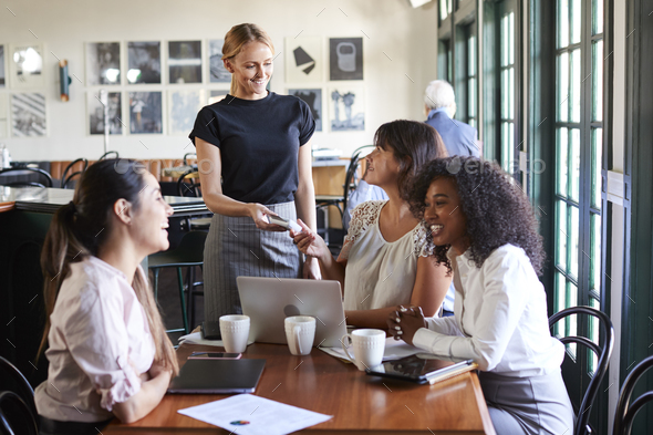 Businesswomen Paying Bill At Meeting Around Table In Coffee Shop - Stock Photo - Images
