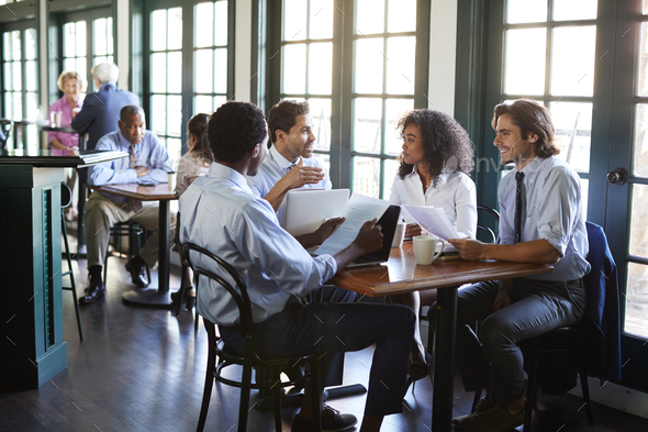 Business Team Having Informal Meeting Around Table In Coffee Shop - Stock Photo - Images