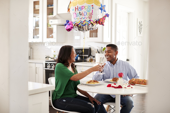 Black couple making a toast over a romantic birthday meal in their kitchen - Stock Photo - Images
