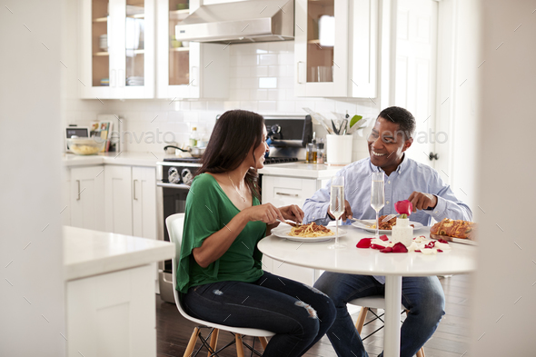 Middle aged mixed race couple eating a romantic meal together in their kitchen, close up - Stock Photo - Images