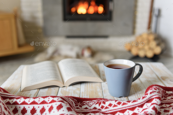 Book and cup of tea near fireplace - Stock Photo - Images