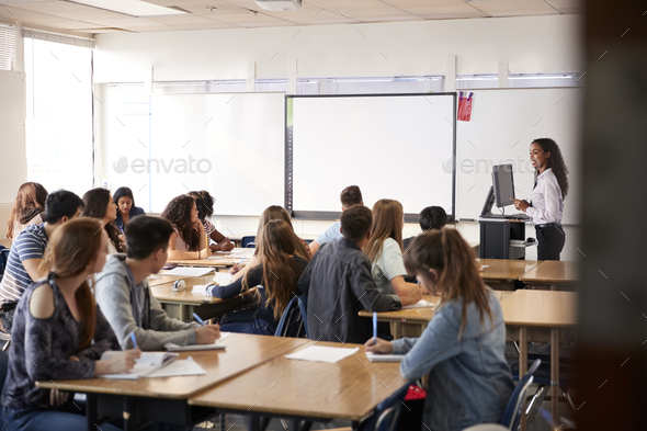 Female High School Teacher Standing By Interactive Whiteboard Teaching Lesson - Stock Photo - Images