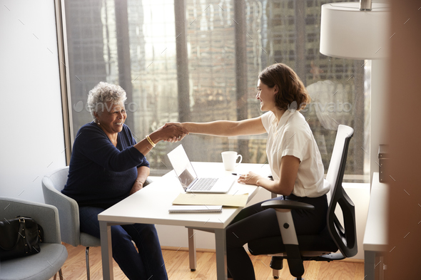 Senior Woman Shaking Hands With Female Doctor In Hospital Office - Stock Photo - Images