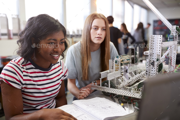 Two Female College Students Building Machine In Science Robotics Or Engineering Class - Stock Photo - Images