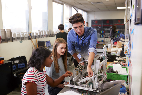 Teacher With Two Female College Students Building Machine In Science Robotics Or Engineering Class - Stock Photo - Images