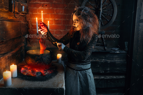 Scary witch cooking soup with human body parts - Stock Photo - Images