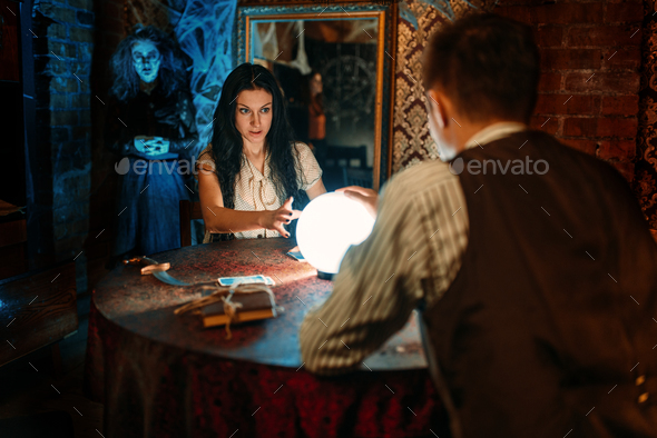 Couple on spiritual seance, witch on background - Stock Photo - Images