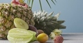 Freshly picked natural ripe exotic fruits with ripe pineapple on a wooden gray table on a blue - PhotoDune Item for Sale