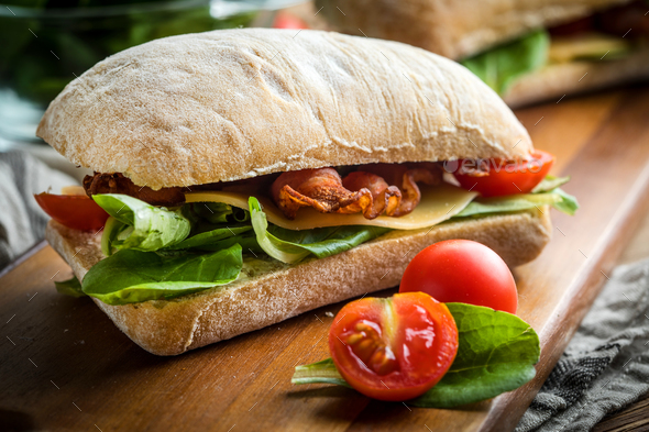 Ciabatta sandwich with arugula salad, bacon and yellow cheese. - Stock Photo - Images