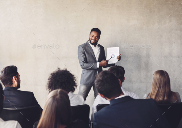 Successful businessman presenting diagrams to colleagues on training - Stock Photo - Images