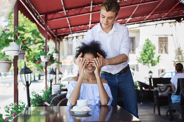 Handsome man covering eyes to her girlfriend - Stock Photo - Images