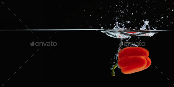 Colored orange paprika in water splashes on black background - Stock Photo - Images