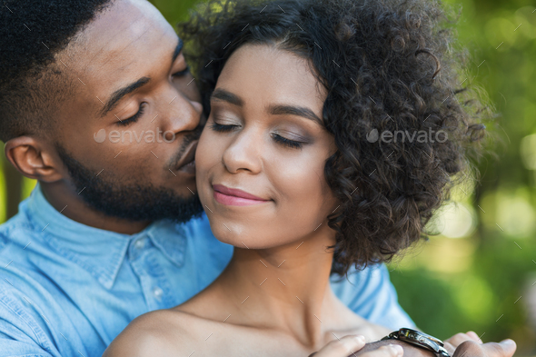 Handsome man kissing tenderly his girlfriend in cheek - Stock Photo - Images