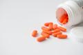 Orange pills cascading out of white bottle - PhotoDune Item for Sale