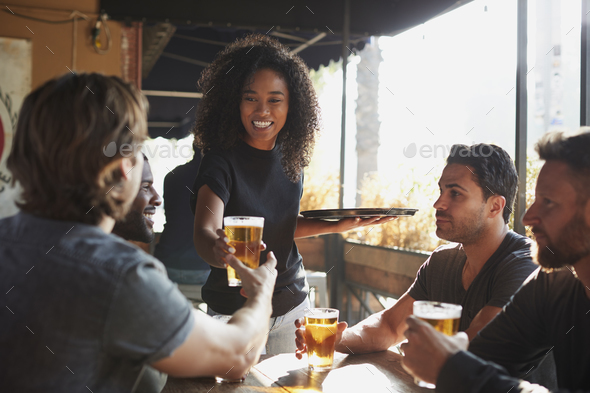 Waitress Serving Drinks To Group Of Male Friends Meeting In Sports Bar - Stock Photo - Images